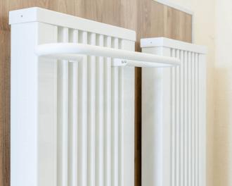 """De handdoekdroger kan eenvoudig bovenin tussen de lamellen van een elektrische radiator """"gehangen"""" worden. De bij de radiator meegeleverde afdekking kan teruggeplaatst worden, over de beugels van de handdoekdroger."""